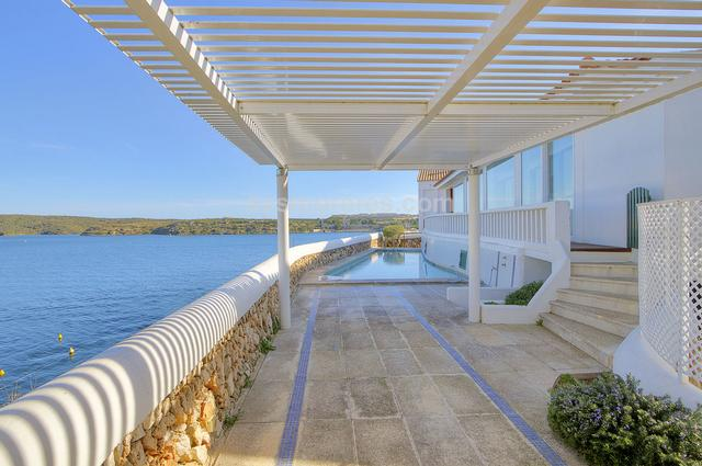 This magnificent villa is located in a front-line position in the port of Mahon, in a very quiet residential area in front of the famous bay of Calas Fonts. Its elevated position provides incredible views of much of Mahon harbour.  It is a very spacious and bright house with a relaxed and cosy atmosphere, with outdoor areas such as the large covered terraces, its inner courtyard, and a garden full of plants and shrubs. The property also offers a very comfortable layout with a large kitchen, dining room, living room, and a loft area which would be ideal as a library or office. It has all the amenities required of a luxury property: underfloor heating, water softener, double glazing and a garage. Built surface 289 m², 760 m² plot,  4 bedrooms (1 suite,  3 double),  2 bathrooms, kitchen, laundry room, dining room, terrace, garden, garage, built-in wardrobes, underfloor heating, double glazing, fireplace, swimming pool, front line, sea view, storage room.  Energy certif. (E) 233,0000 Kwh/m²a.