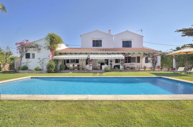 This beautiful villa is located in the village of Trebaluger, with easy access to both Sant Lluis and Es Castell.  It sits on a peaceful corner plot with a well maintained garden and pool.  The house has a large covered terrace which provides ample shady area for meals and relaxing in the summer whilst for the winter months there is a wood burning stove in the comfortable lounge, as well as under floor heating throughout.  There are three double bedrooms, two bathrooms and a cloakroom on the ground floor, also the double garage and the kitchen which includes a breakfast room and a storeroom. On the first floor is a spacious second lounge, terrace, bedroom with en suite bathroom and dressing room, this area could easily be converted into an apartment if required. Built surface 345 m²,  4 bedrooms (4 double),  3 bathrooms,  1 cloakroom, kitchen, utility room, dining room, terrace, garden, garage, built-in wardrobes, underfloor heating, double glazing, fireplace, air conditioning, Energy Efficiency ´C´, 80 Kw h / m²a, Emissions (D) 22 Kg CO2 / m²a.