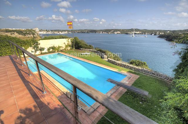 A unique house in the port of Mahon with its own mooring and spectacular views. It is a two-storey house of approx. 400m2 on a prime waterfront plot of 1,200 m2. The house has an incredible design that maximizes the natural light and is arranged with large open spaces that make a total of 6 bedrooms and 4 bathrooms, garage, terraces, mature gardens, swimming pool of approx. 50m² surface area, and a large, deep mooring with a storeroom. Without a doubt this is one of the most exclusive properties in Mahon harbour.