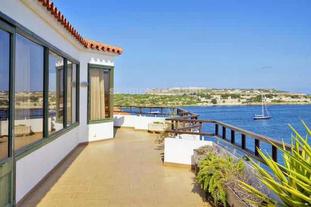 Singular penthouse with unparalleled panoramic views of the entrance of the port of Mahon, the picturesque port of Calas Fonts and the town of Es Castell. The penthouse built in the 70s is well preserved with some of its spaces renovated over time. The property would benefit from a modernization of its interior. A totally exclusive elevator for the property leads directly into the spacious hall of the house. The bright and spacious living room enjoys the best views over the entrance of the port of Mahón and bathes in the first sun of Spain at dawn. A large terrace surrounds the entire property and can be accessed from all areas of the house. A very spacious kitchen with its dining area connects with the living room. There are a total of 3 bedrooms and 2 bathrooms, of which one is a suite with a large window, dressing area and an office that could be converted into another bedroom. From the inside of the house there is a direct access to the upper terrace of the building. Optional parking space.