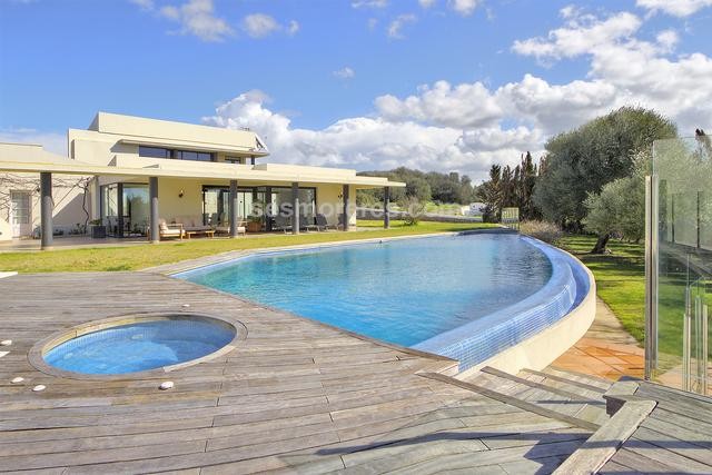Stunning villa with  a modern design located in a rural setting within walking distance of the village. The house has all kinds of comforts and a carefully thought design. Its wide spaces open to the outside, offering a cosy and very bright atmosphere and with beautiful views. Highlighting its large master suite with large windows and private terrace. On the ground floor there is a living room with fireplace, 3 double bedrooms, 3 bathrooms, a large fully equipped kitchen with access to the outside terrace, a laundry room and a small cellar. A beautiful glass patio leads to a large dining room - living room. The well kept garden has large areas of lawn, a large 80m2 designer swimming pool with jacuzzi and large solarium. A porch with a rustic design, houses the barbecue area with its own stone oven to enjoy great evenings outside. In the basement we find a heated pool with a wellness area prepared for a sauna. The house is equipped with central heating, air conditioning and piped music. The garage has capacity for several cars and there is a large outdoor parking area. The property also has a large plot of 17,868 m2.