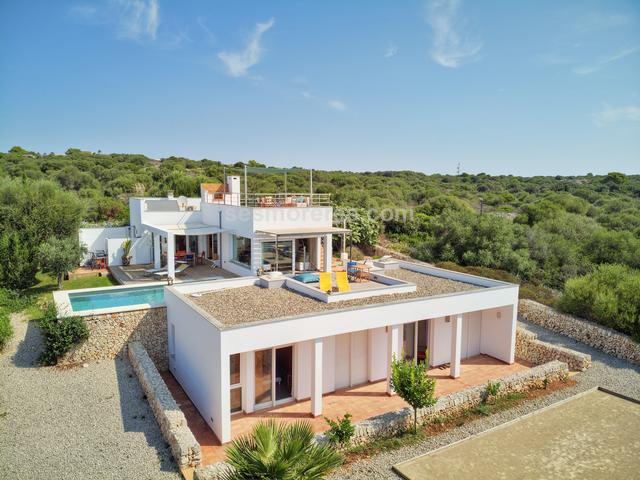 A stunning recently-built contemporary villa with amazing views over the south coast of the island. This villa of 247m² is finished with high-quality finishes on a plot of 1002m² in one of the most exclusive parts of Binibeca. On the ground floor the entrance hall leads through to a spacious living/dining room, a separate kitchen with utility room, and cloakroom, and the living areas lead to large terraces and the swimming pool with amazing sea views
