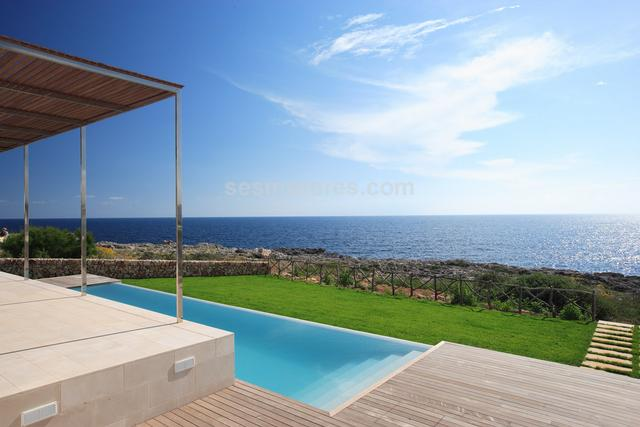 Luxurious contemporary designer villa in front-line position, located near the picturesque fishing village of Binibeca Vell and the beautiful Binibeca beach. Its spacious and glazed living room and dining room offer spectacular views of the sea. The spectacular large kitchen is of an Italian design and equipped with high quality fittings.