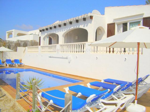 Villa divided in two totally independent apartments that share the garden areas and swimming pool. It is located near the seafront in Binibeca Vell. Built surface 97 m², 420 m² plot,  4 bedrooms (4 double),  2 bathrooms, kitchen (two fully equipped kitchens), dining room, terrace, furnished, swimming pool.